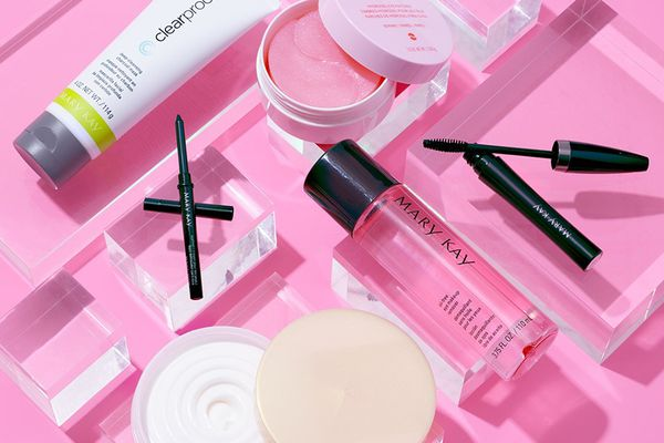 A selection of Mary Kay products on a pink background.