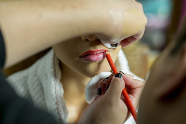 woman getting lip liner applied