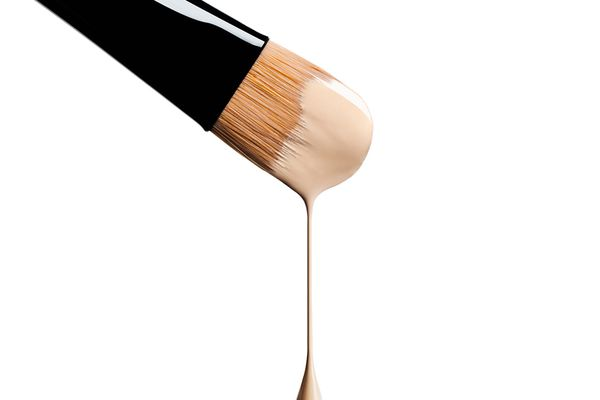 makeup brush dripping with liquid foundation