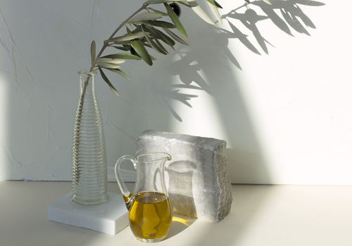 Olive oil in a pitcher and an olive branch in a vase