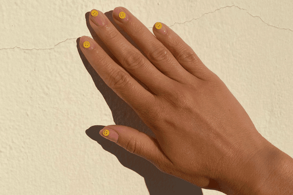 woman with smiley face manicure