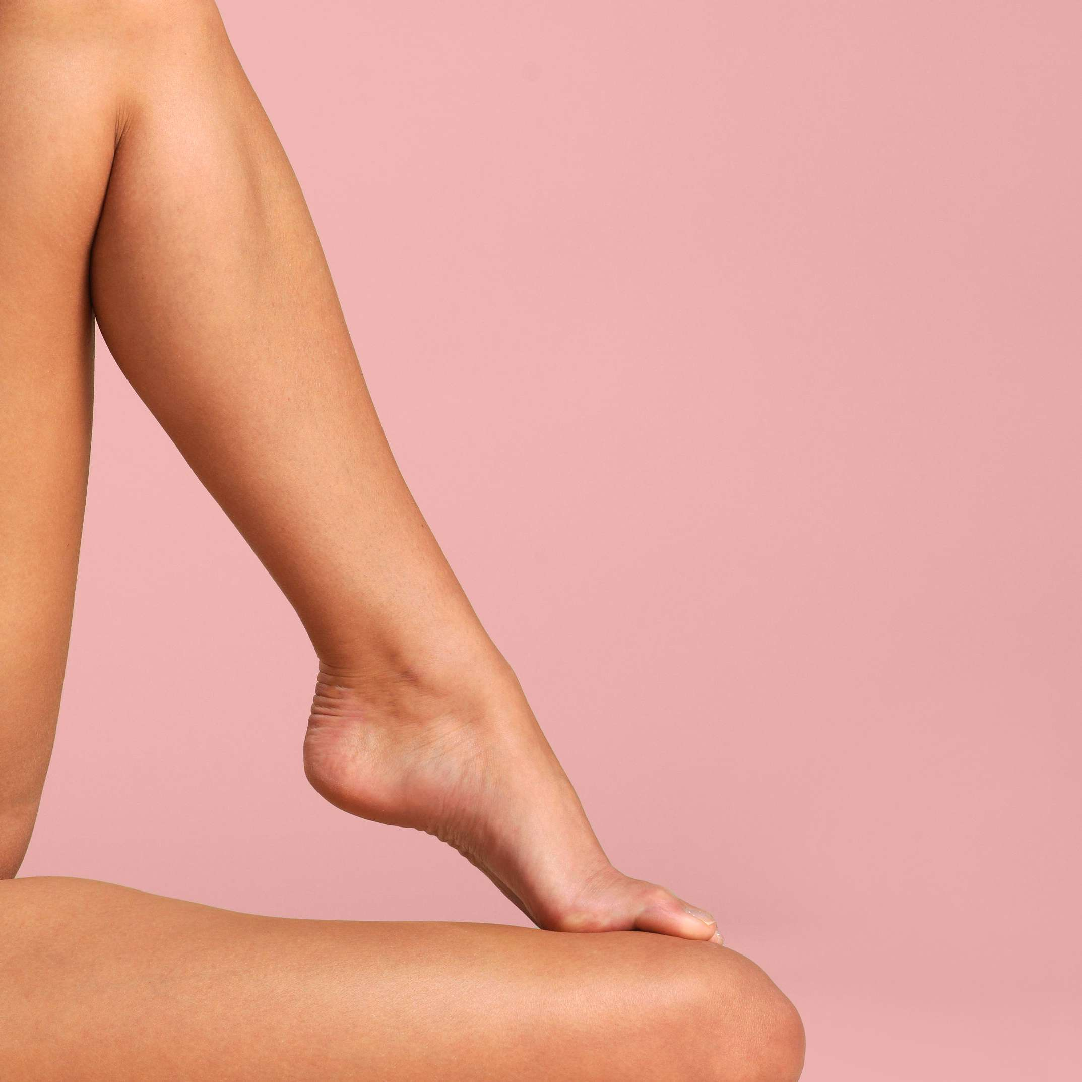 Woman's legs against a pink backdrop