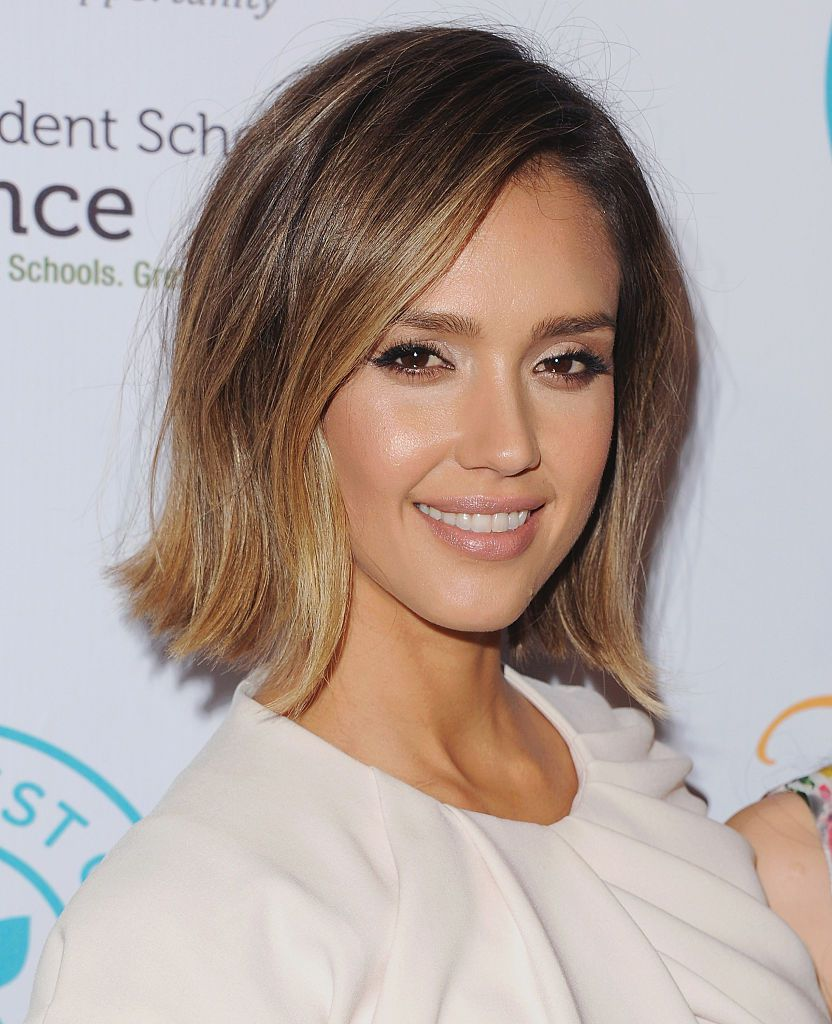 Jessica Alba with short hair in front of a white background.