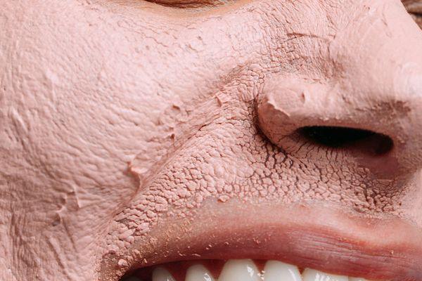 woman with pink clay face mask on