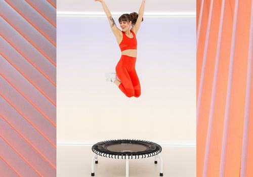 Woman jumping on a trampoline in workout attire