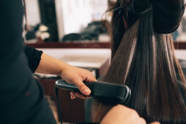 Brown hair being flat ironed in a salon