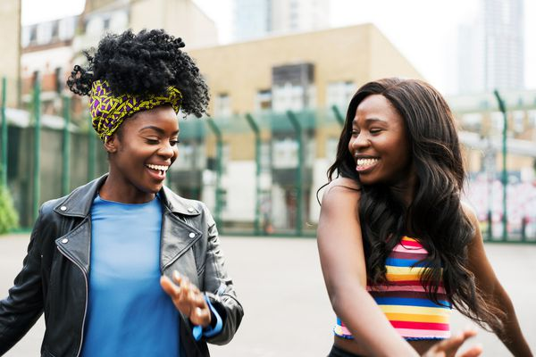 Two black women, one with natural hair and one whose hair has been texlaxed